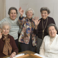 group of happy senior women playing mah-jong with friends waving hello